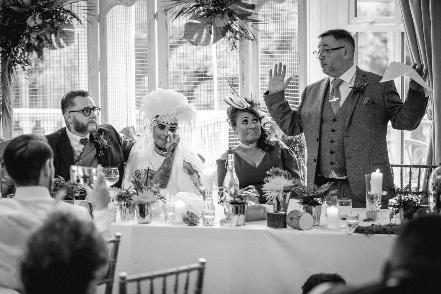 Vintage wedding speeches, father holding hands up and bride crying