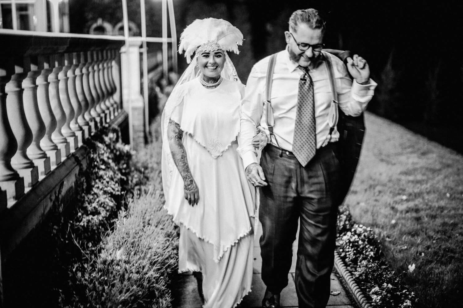Black and white photo of vintage bride and groom walking and laughing