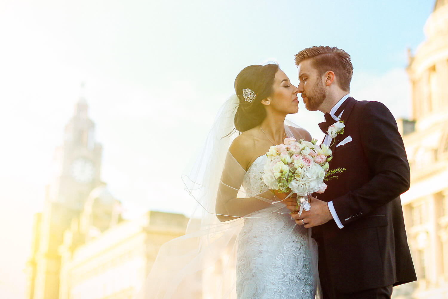 Bide and groom kissing in front of The Venue Royal Liver Building Liverpool
