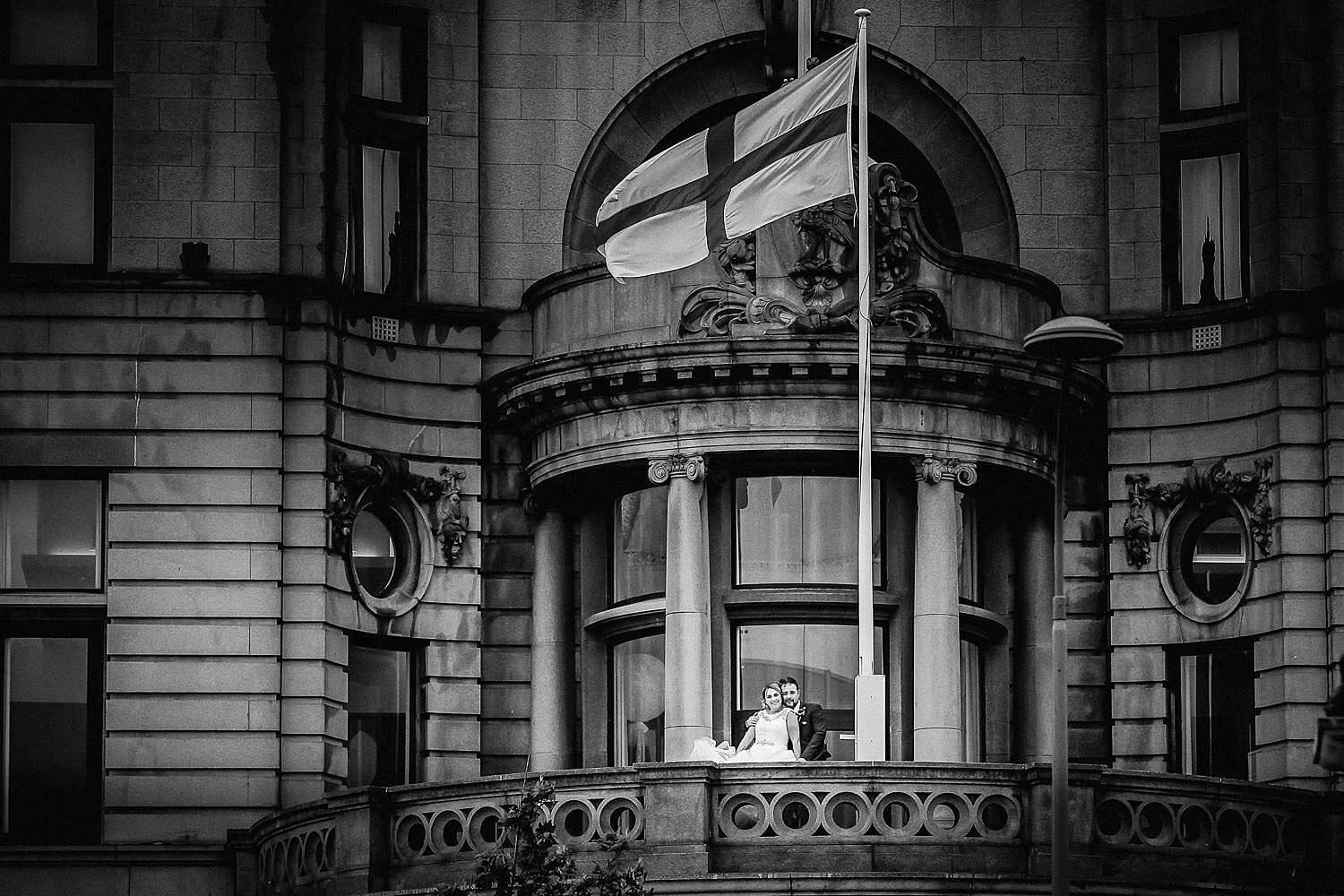 Bride and groom on balcony of Royal Liver Building Liverpool