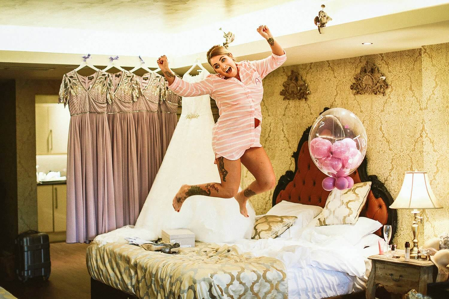 Bride jumping for joy on bead at Shankly hotel Liverpool on wedding morning