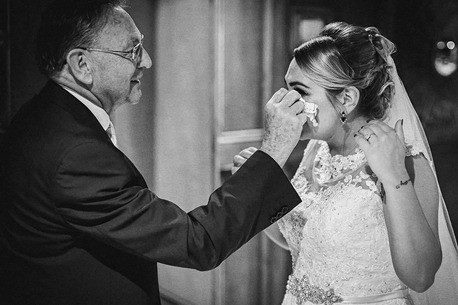 Picture of dad whipping tear from daughter face on wedding day Royal Liver Building wedding photography