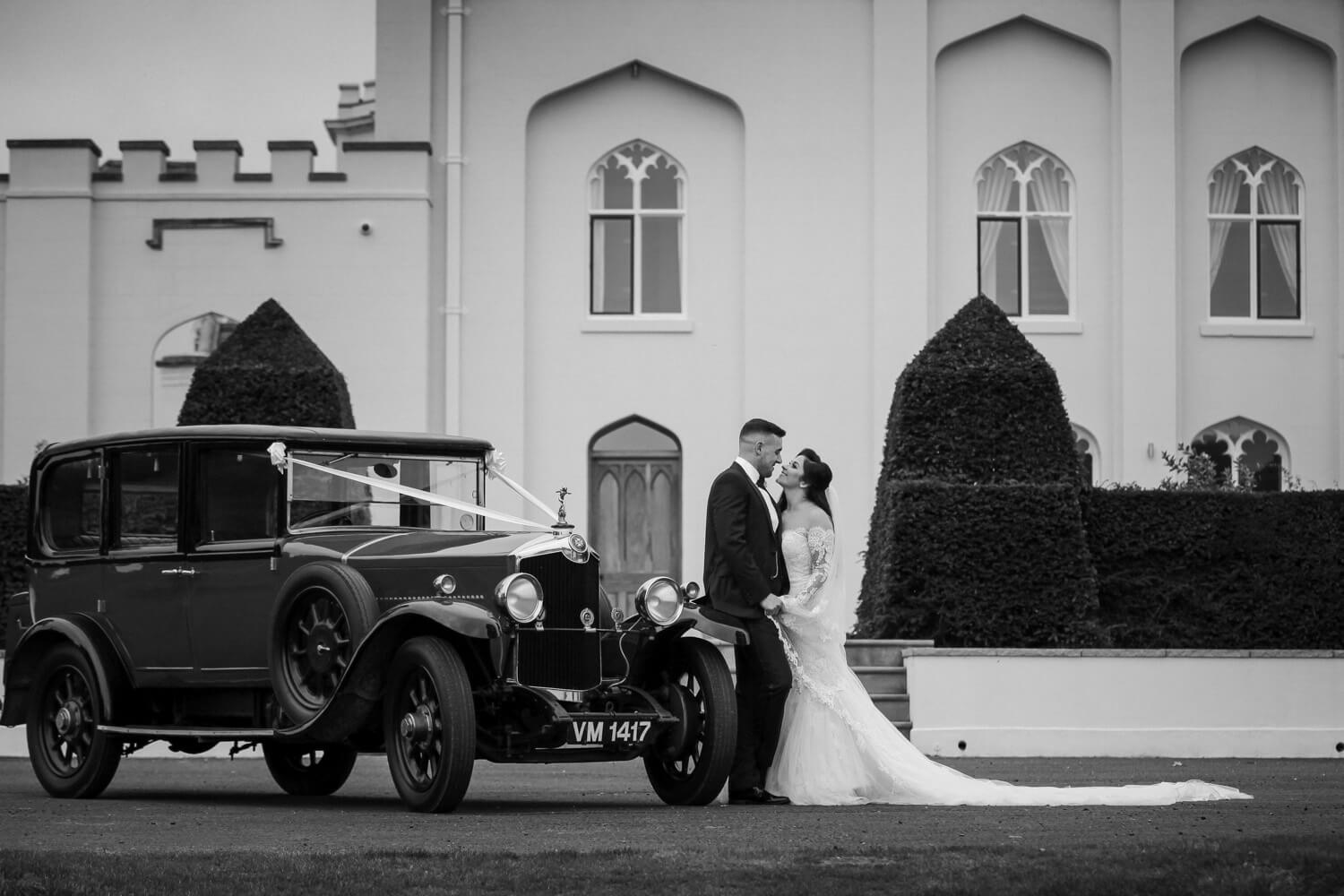Classic black and white photo of bride and groom standing next to classic vintage wedding cat at Combermere Abbey