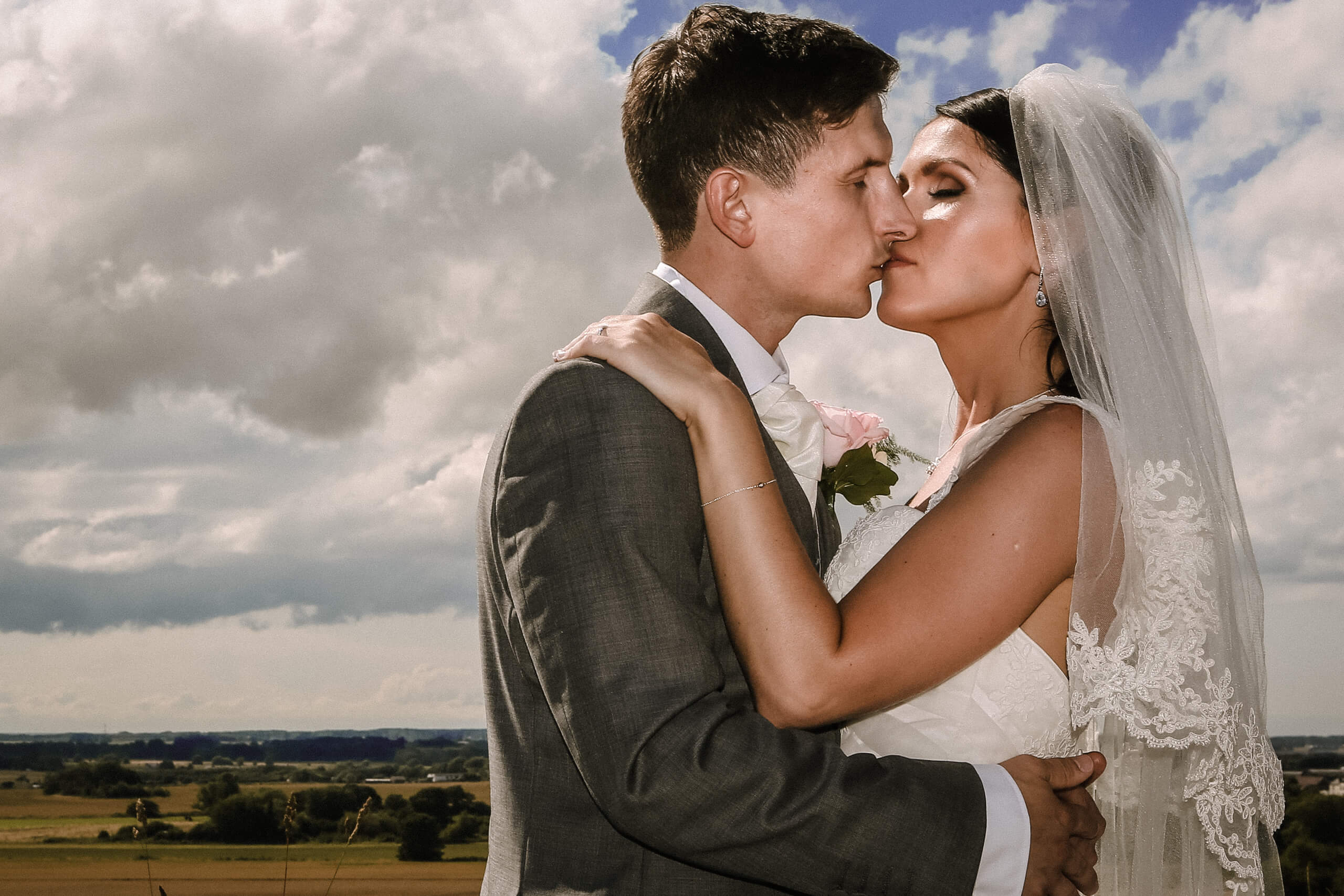 Bride and groom kissing with cloudy sky and lancashire landscape at West Tower