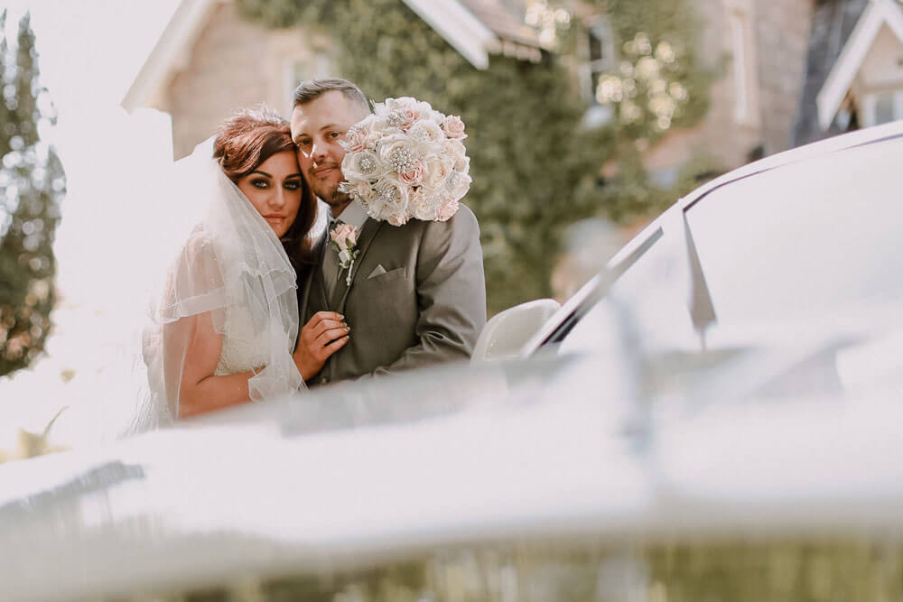 Bride and groom looking at camera behind Rolls Royce holding flowers