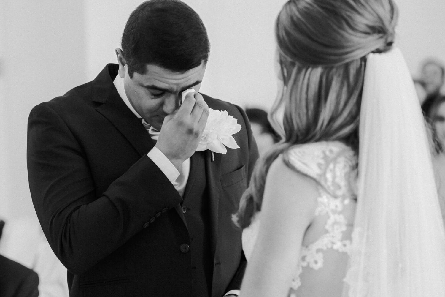 Groom whipping tears during wedding ceremony