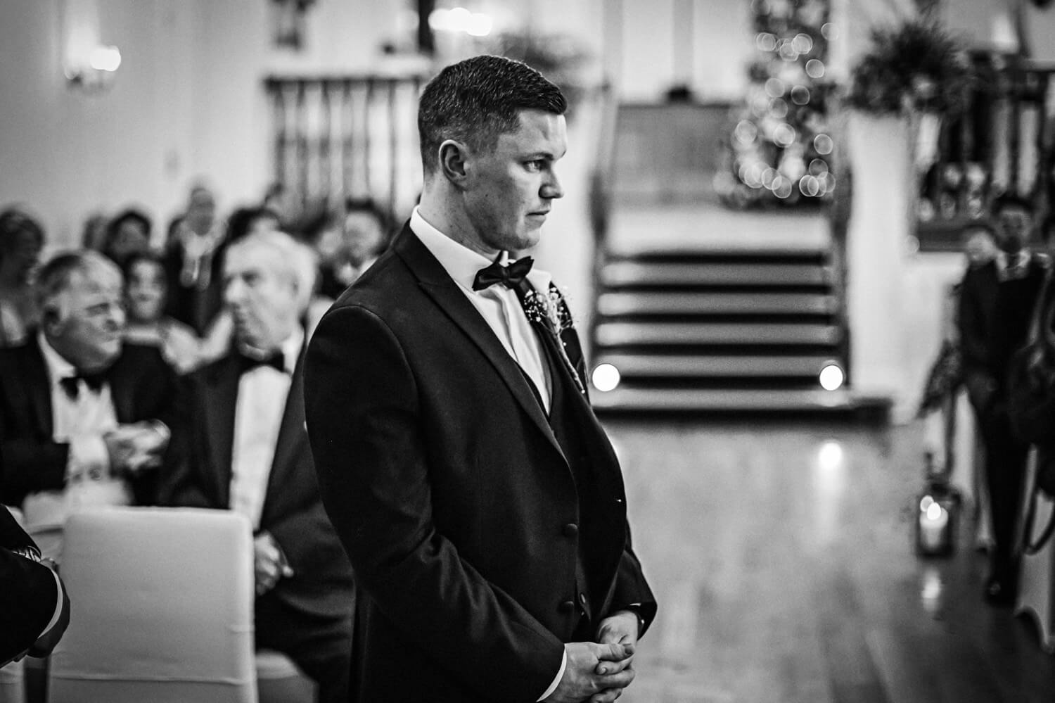Black and white photo of groom waiting