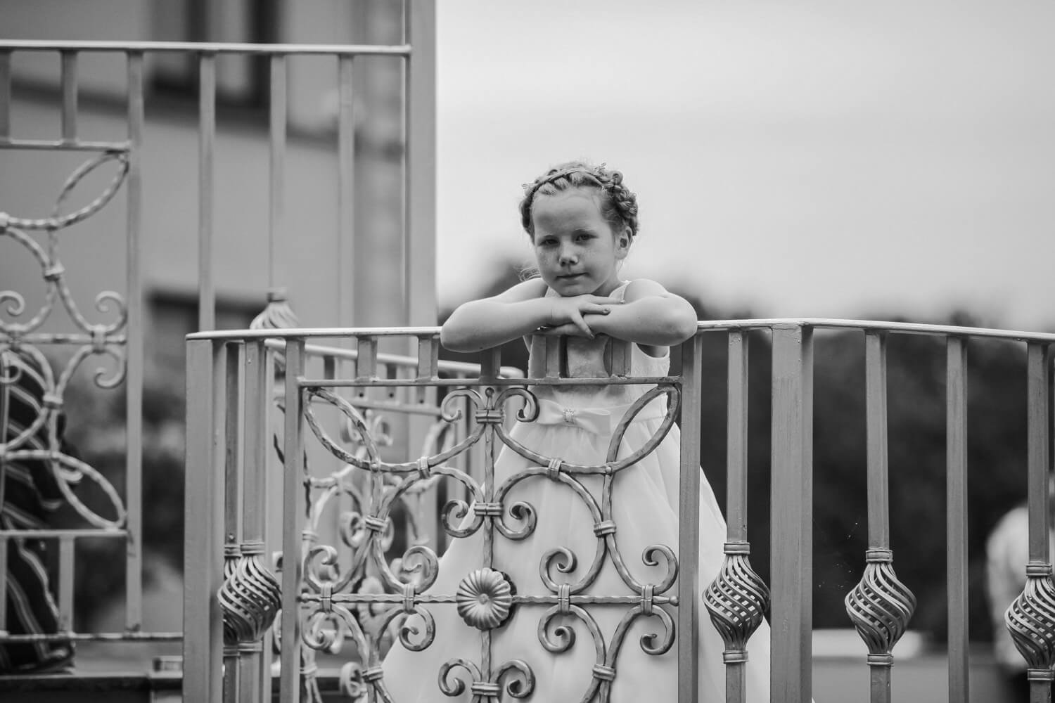Black and white photo of flower girl leaning over railings