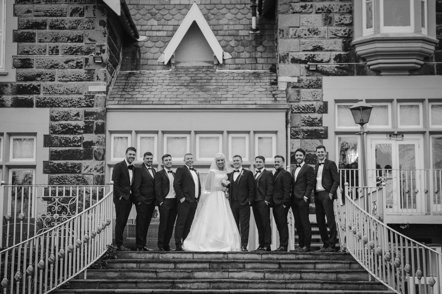 Black and white bridal party photo on steps