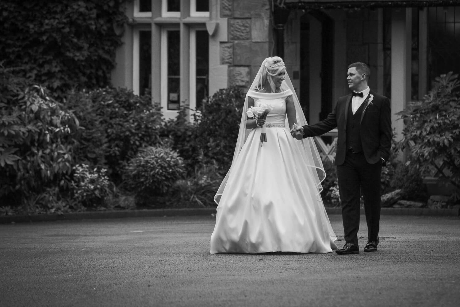Black and white photo bride and groom walking and holding hands