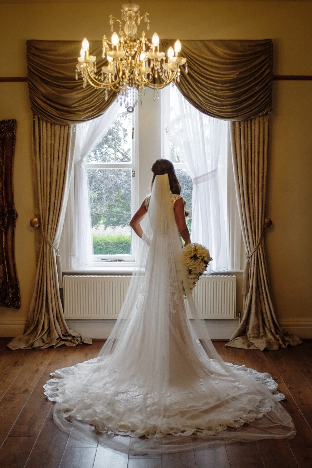 Back of bride standing in bridal suite window