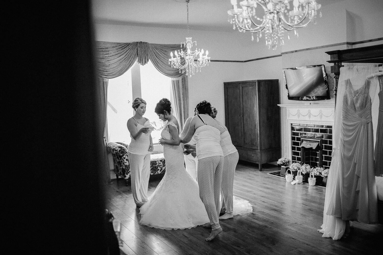 Black and white documentary photos of bridesmaids helping bride get ready