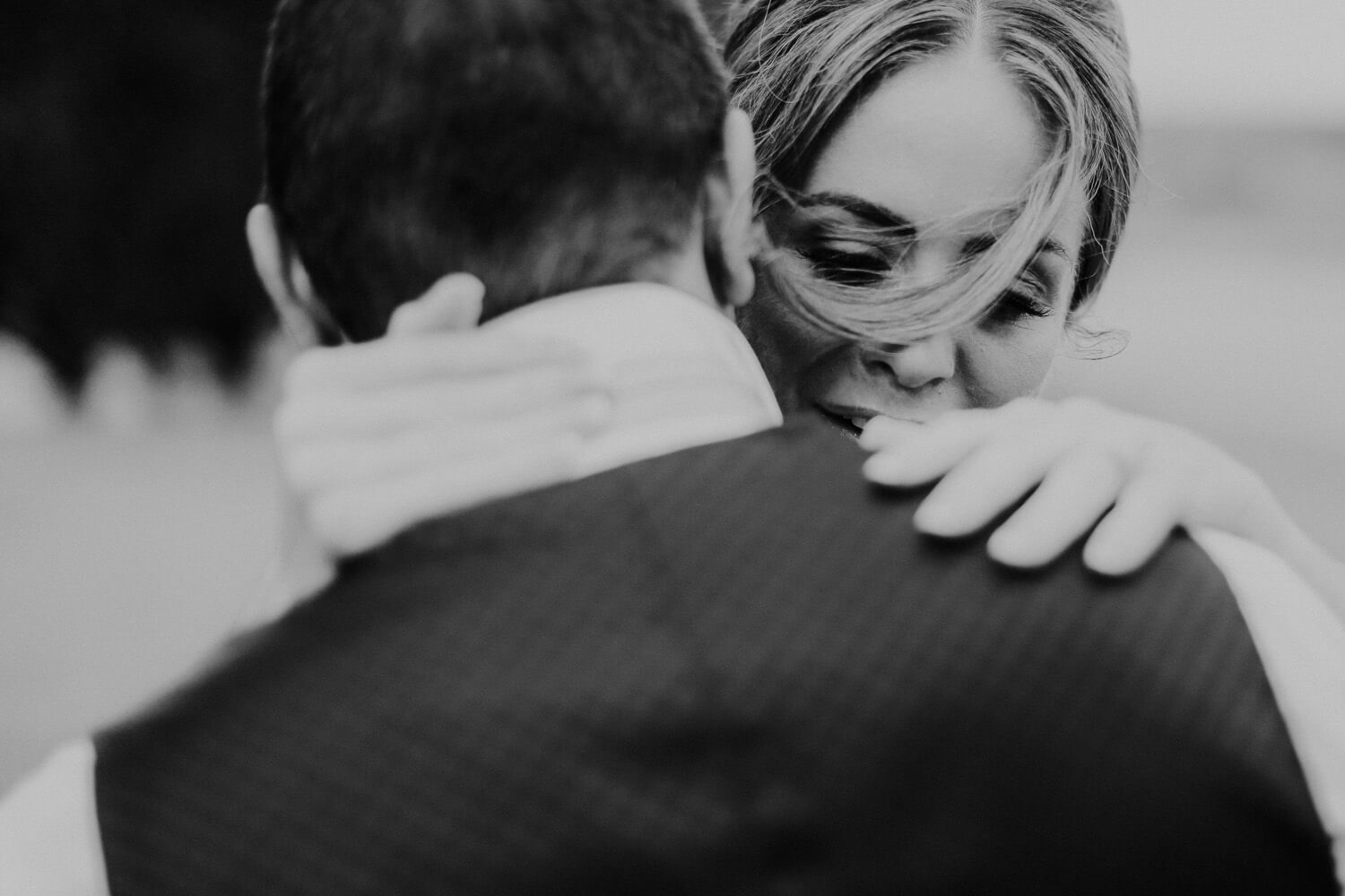 Black and white arty photo of bride hugging groom