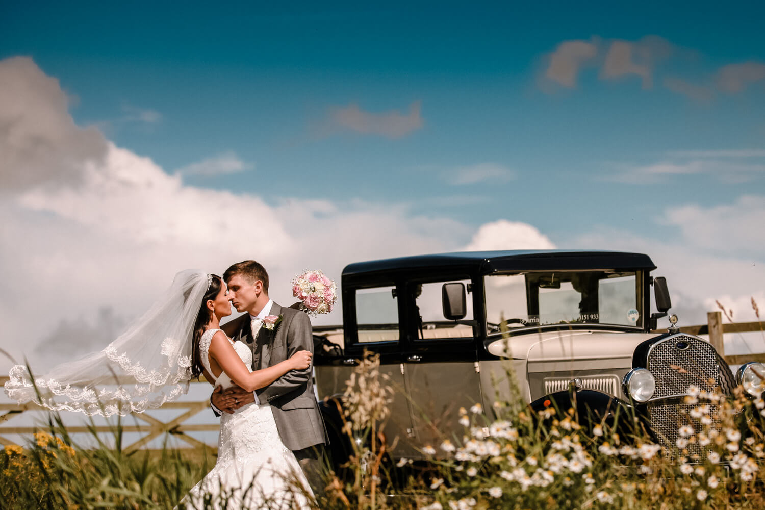 Romantic photo of bride and groom in field with vintage wedding car