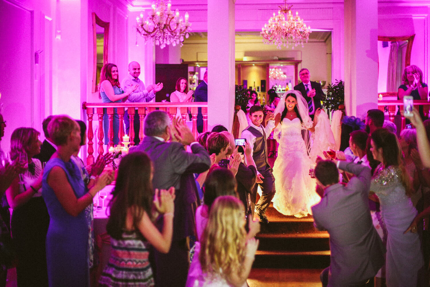 Colourful photo of bride and groom making their way to dance floor