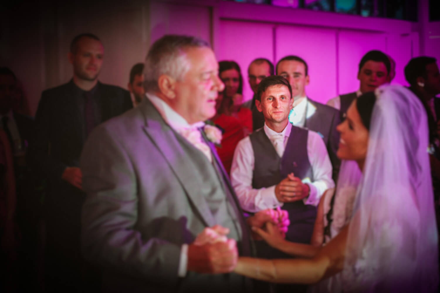 Colourful photo of groom watching bride dance with father