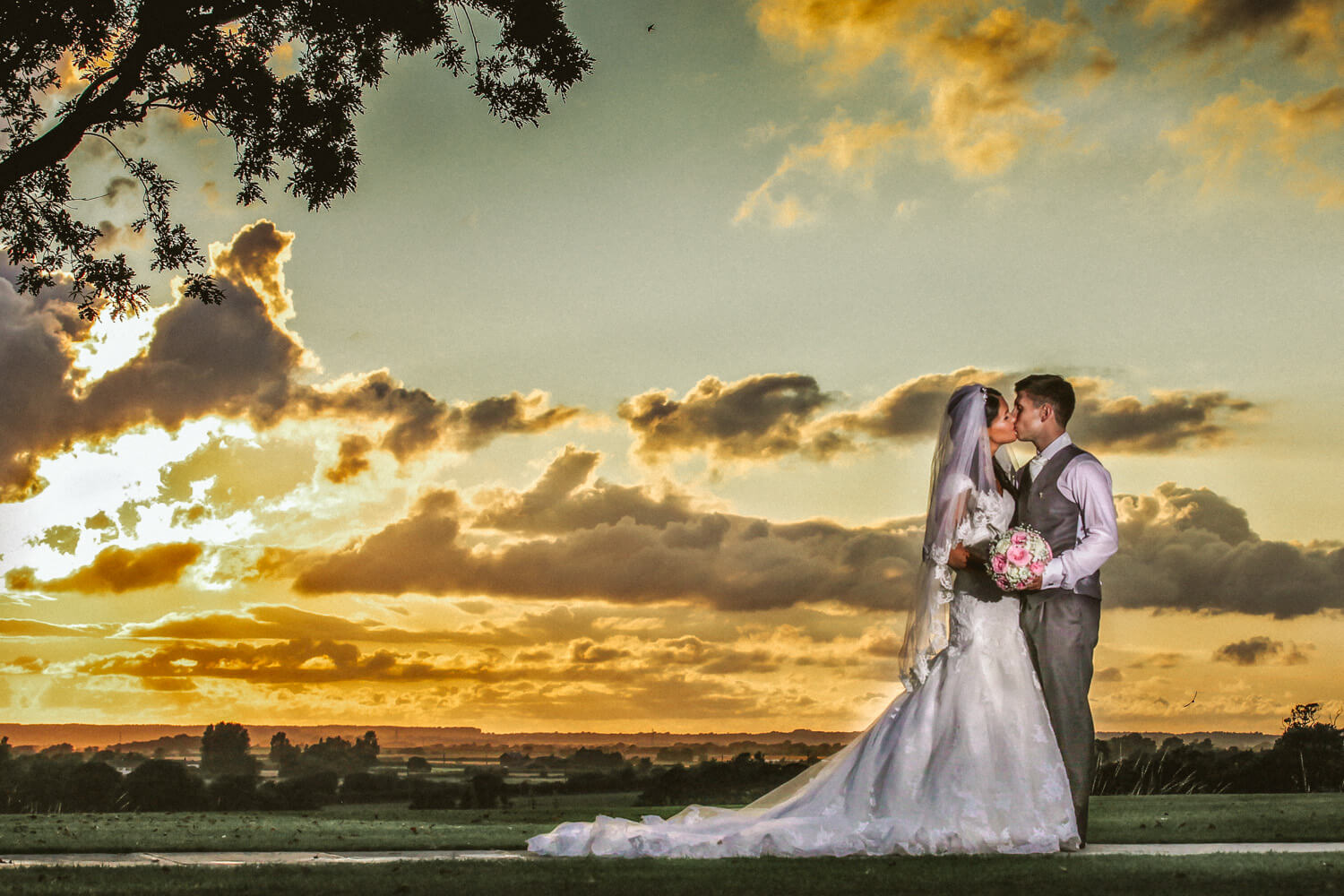 photo of bride and groom kissing with yellow green sunset at West Tower wedding venue Lancashire