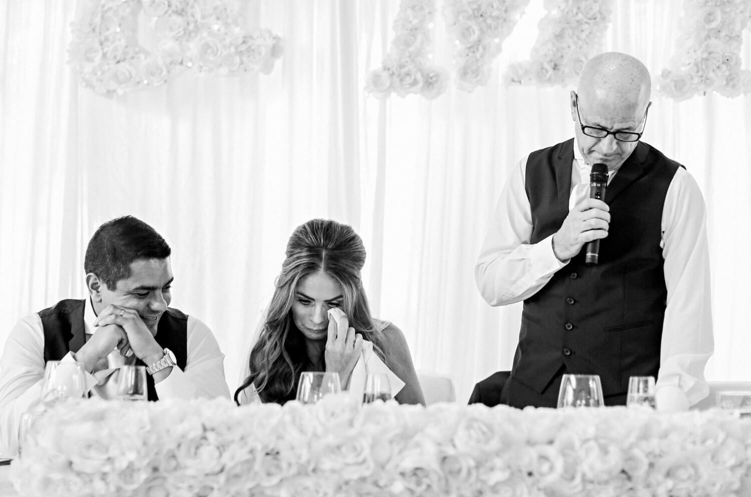 Dad making wedding speech, emotional bride whipping tears