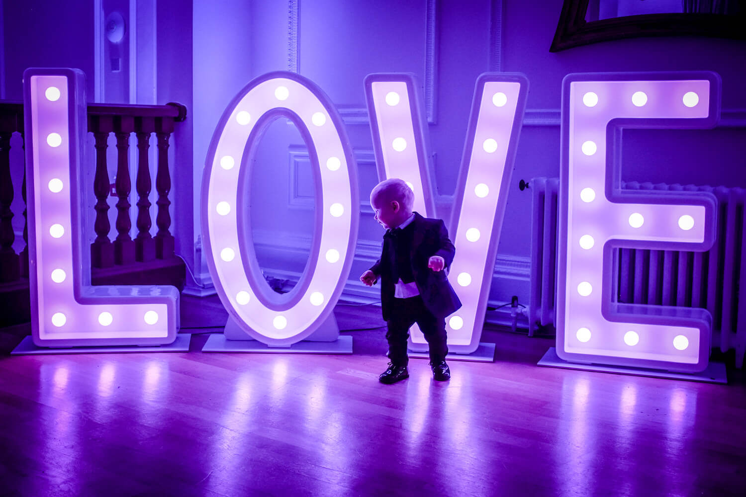 little boy at wedding standing in front of blue love letters