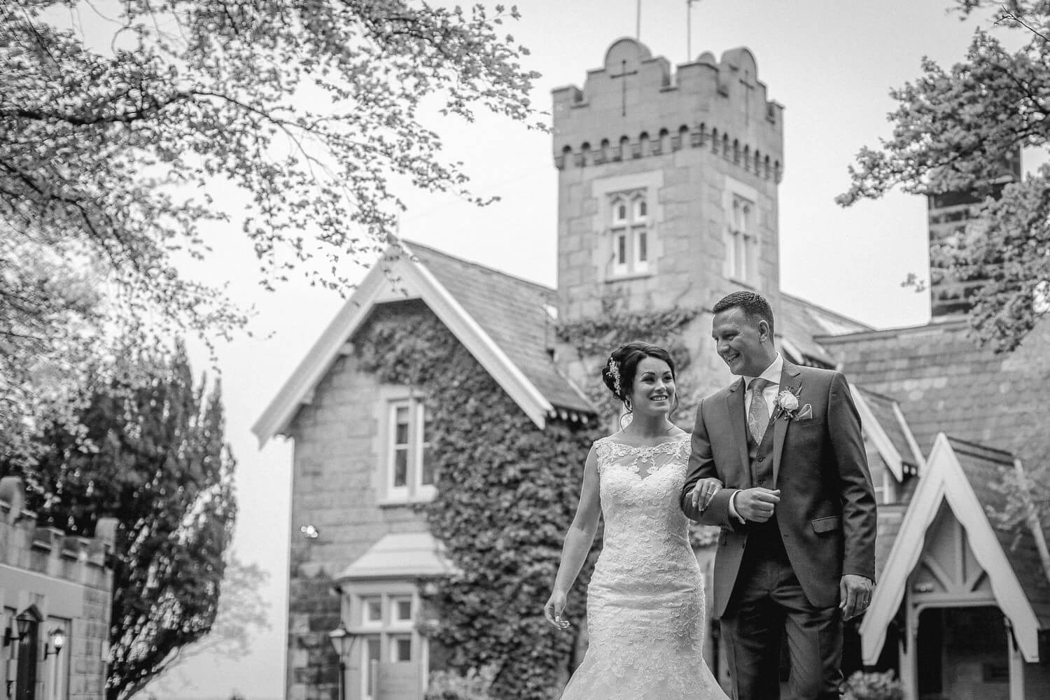 Black and white photo bride and groom walking in front of West tower