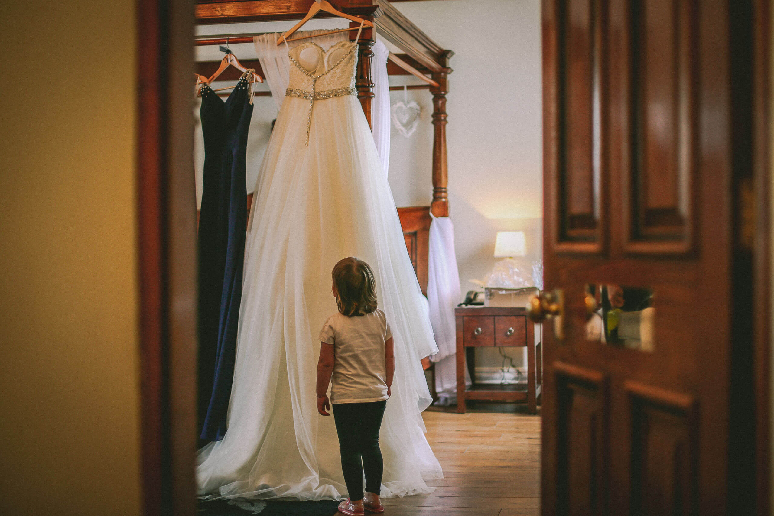 Little girl looking at wedding dress through door of bridal suite West Tower