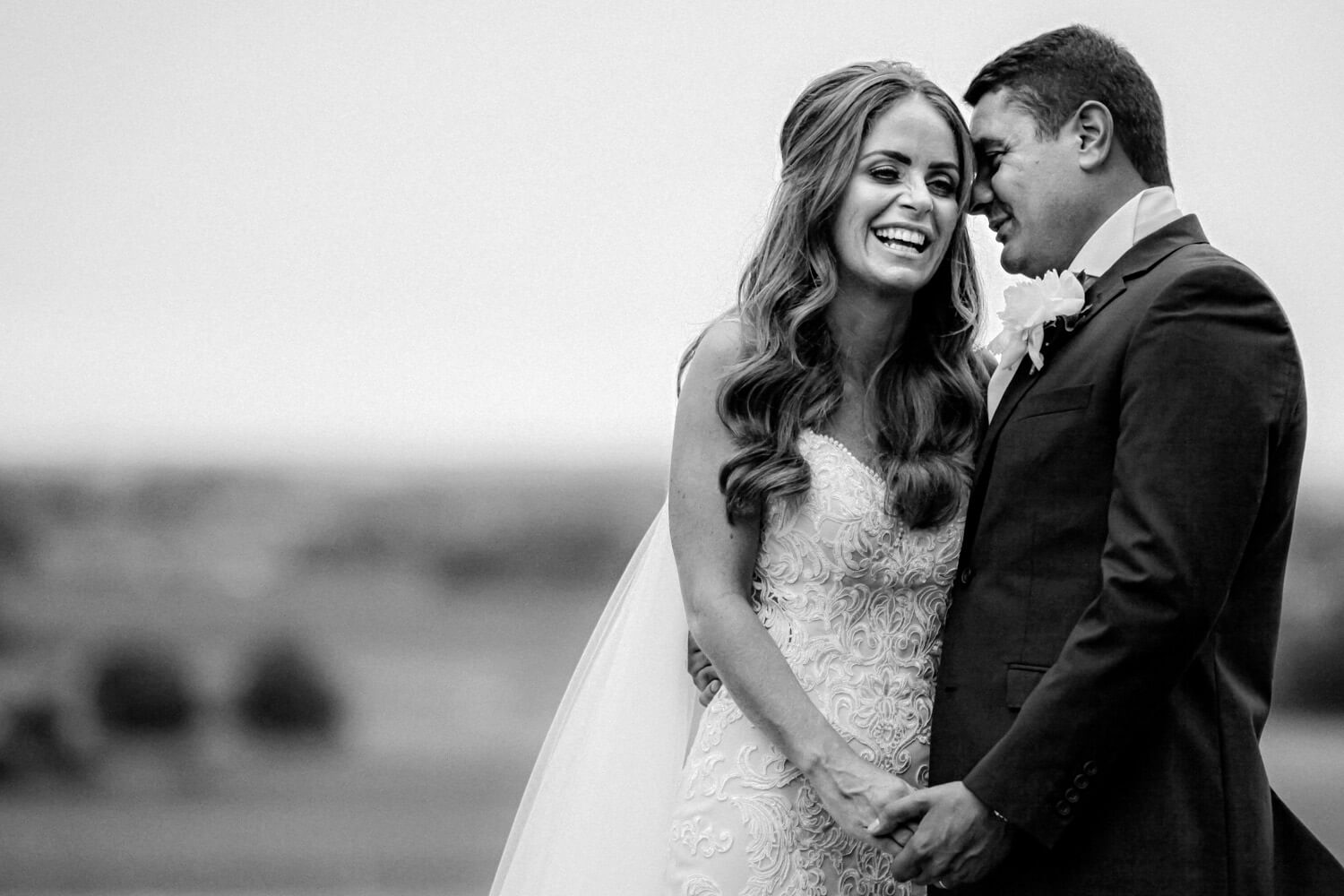 Black and white photo Groom whispering to giggling bride