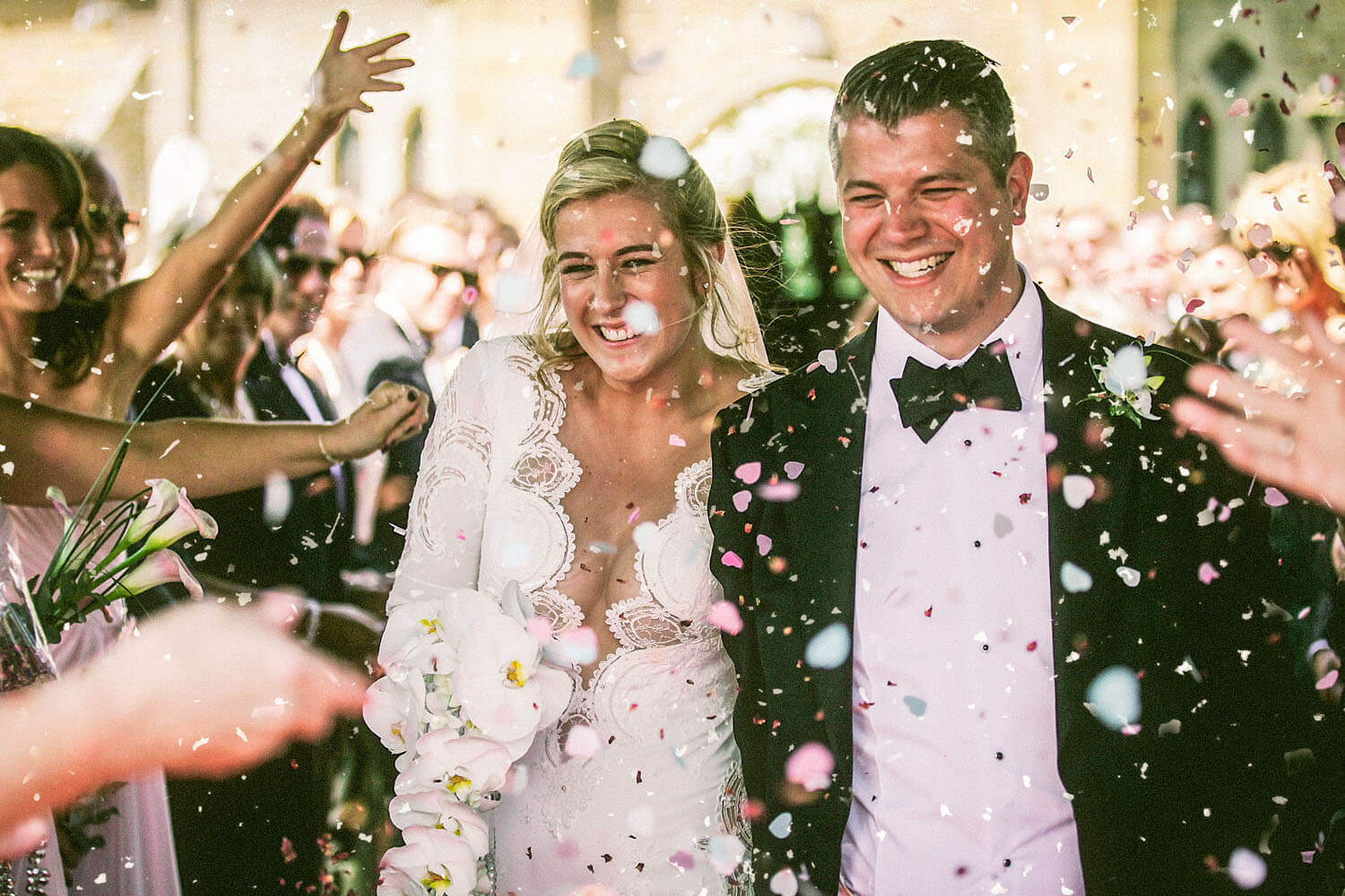 Do I need a 2nd wedding photographer. Bride and groom under confetti