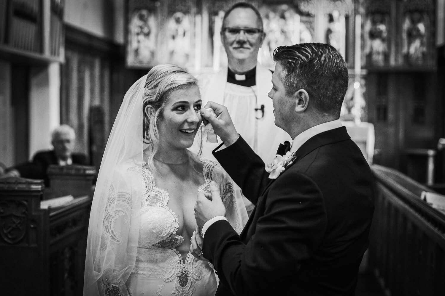 Black and white photo of groom whipping tear from brides face during wedding ceremony