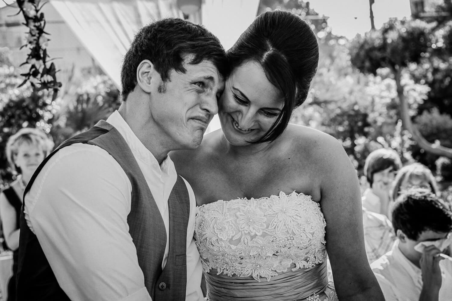 black and white photo of bride and groom crying. How many wedding photographers do I need for my wedding