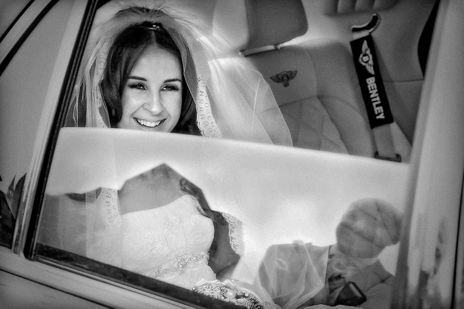 Black and white photo of bride through car window