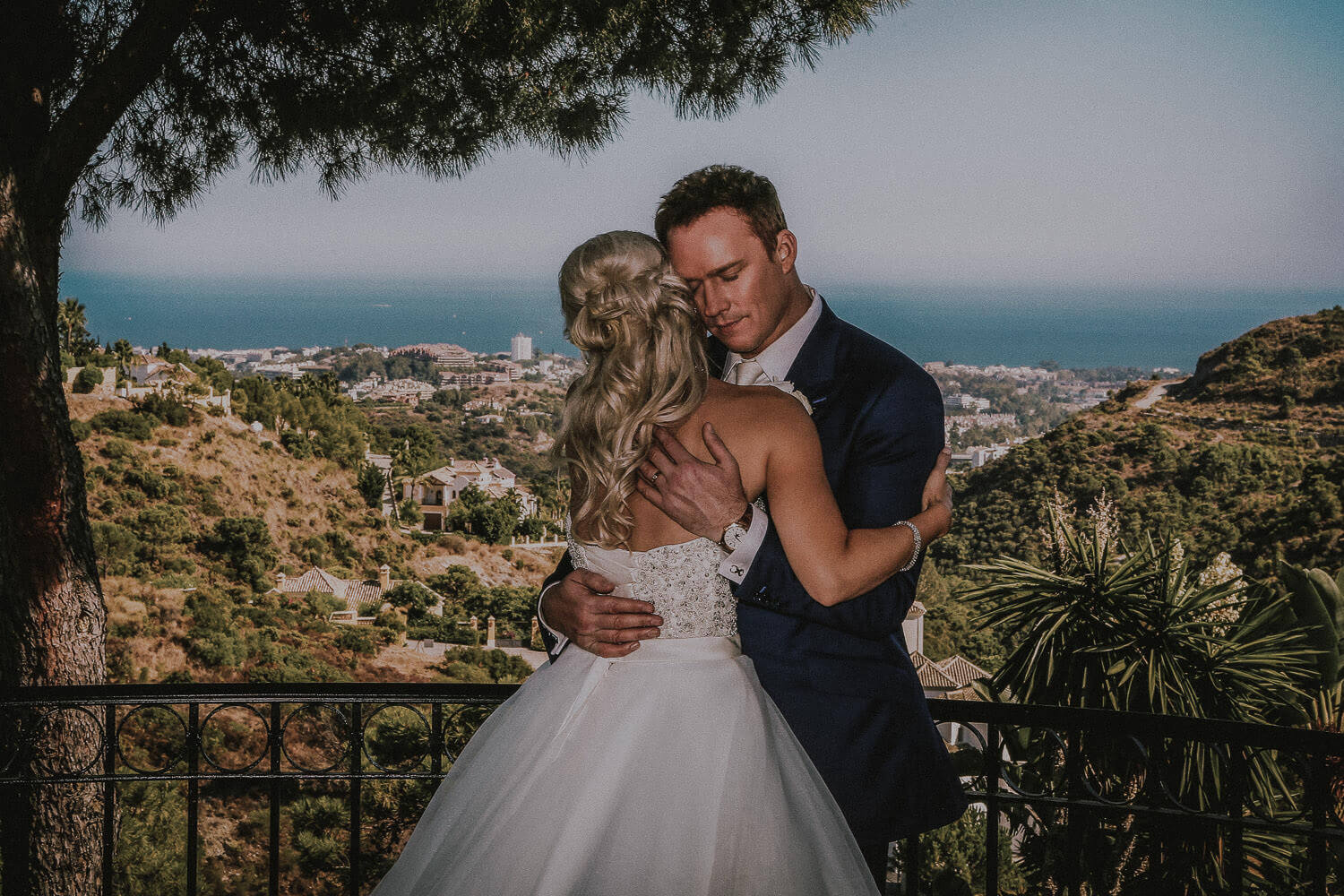 Russell Watson hugging bride on wedding day with Behaves landscape