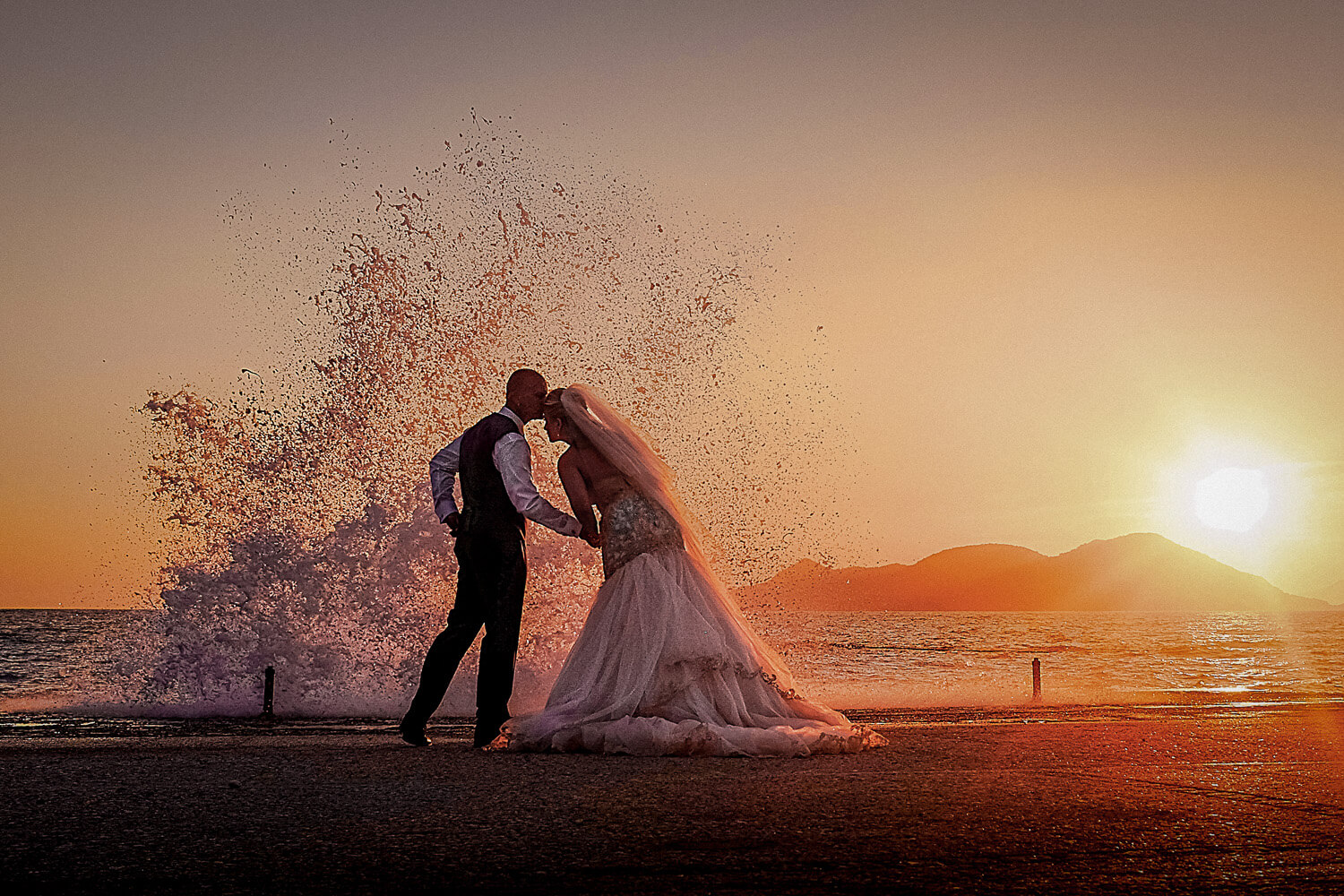 Sun set of wave crashing over bride and groom on wedding day