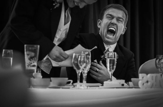 Black and white photo of man laughing during wedding speeches