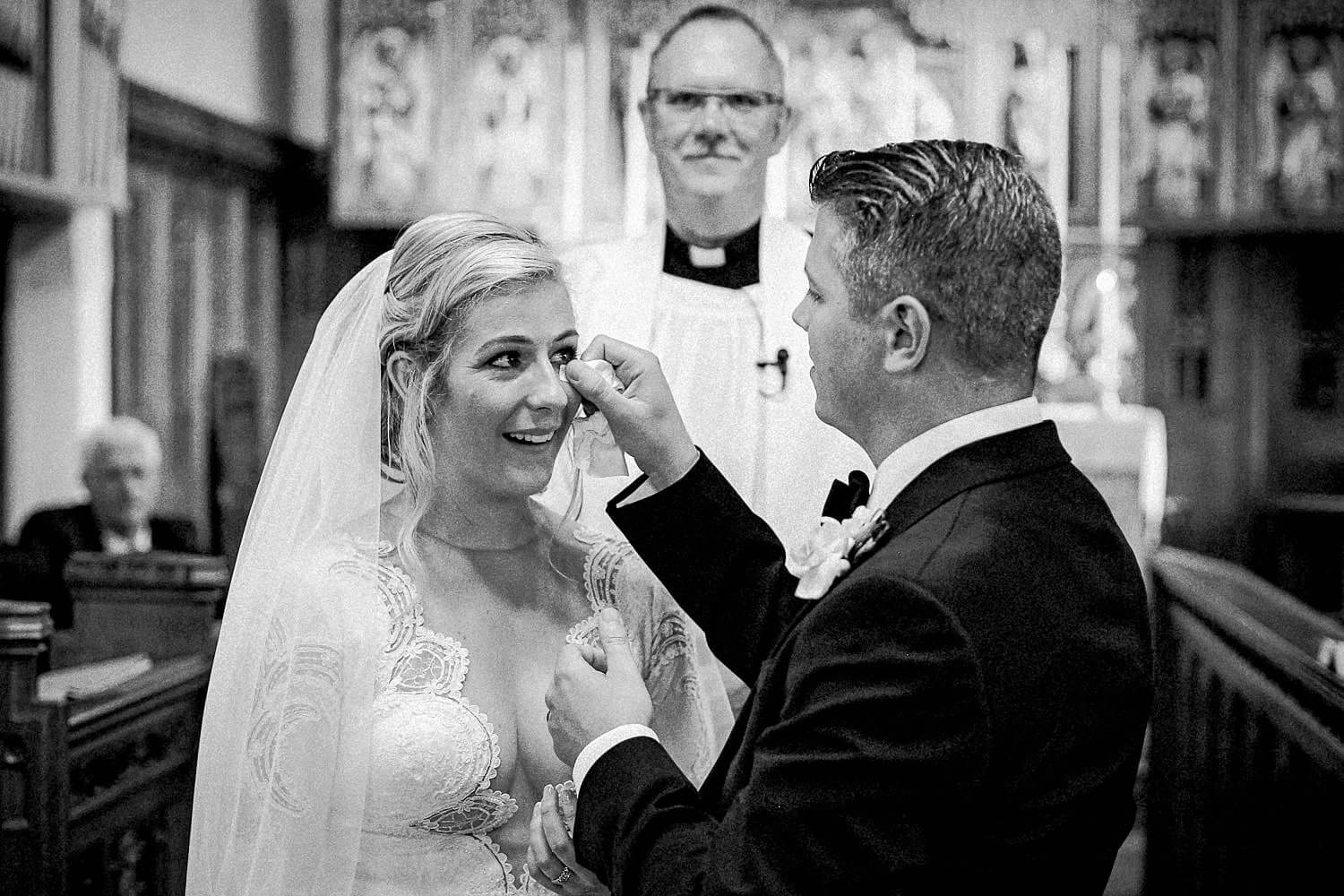 do I need 2nd wedding photographer for wedding. Groom drying brides cry eyes during wedding
