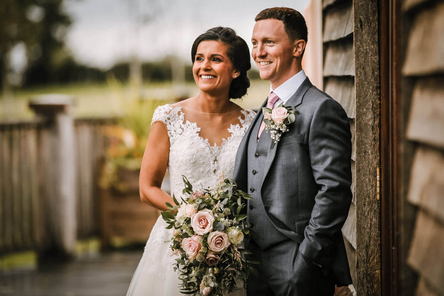 Colourful picture bride and groom smiling Sandhog oak barn by Ormskirk wedding photographer Wes Simpson