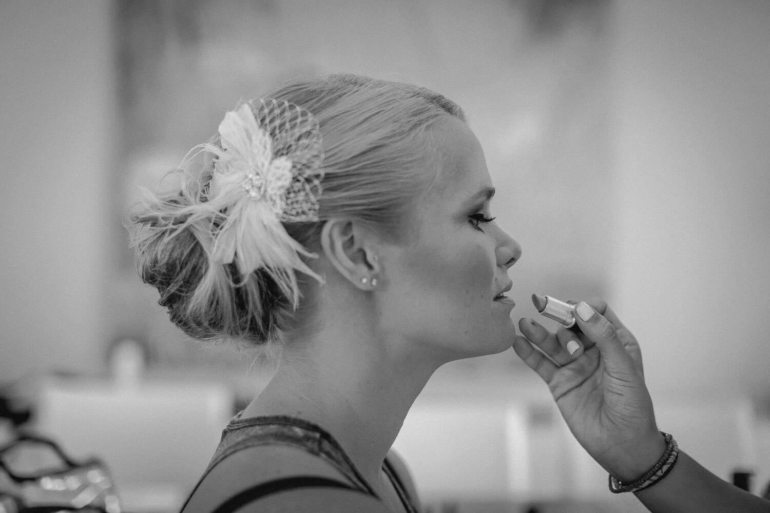 hand applying lipstick to brides lips