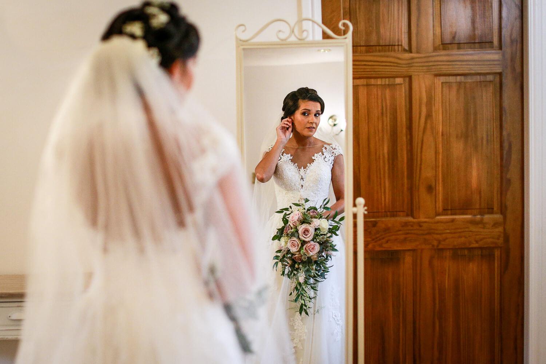 Bride looking into mirror Sandhole Oak Barn wedding photography