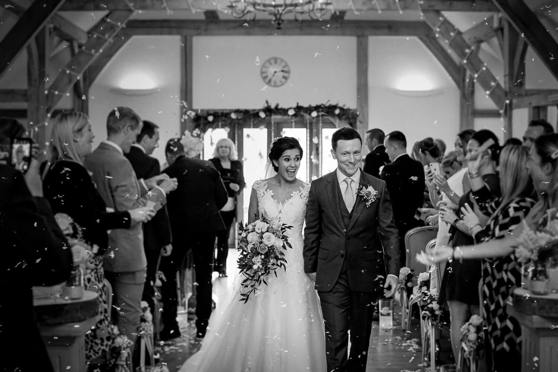 Black and white photo bride and groom walking down the aisleBride walking down the aisle Sandhole Oak Barn