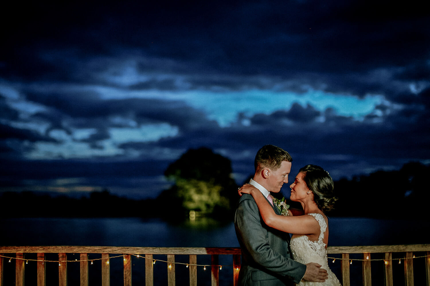 Bride and groom blue sky at night with lake and tree in background. Sandhole Oak Barn wedding photography