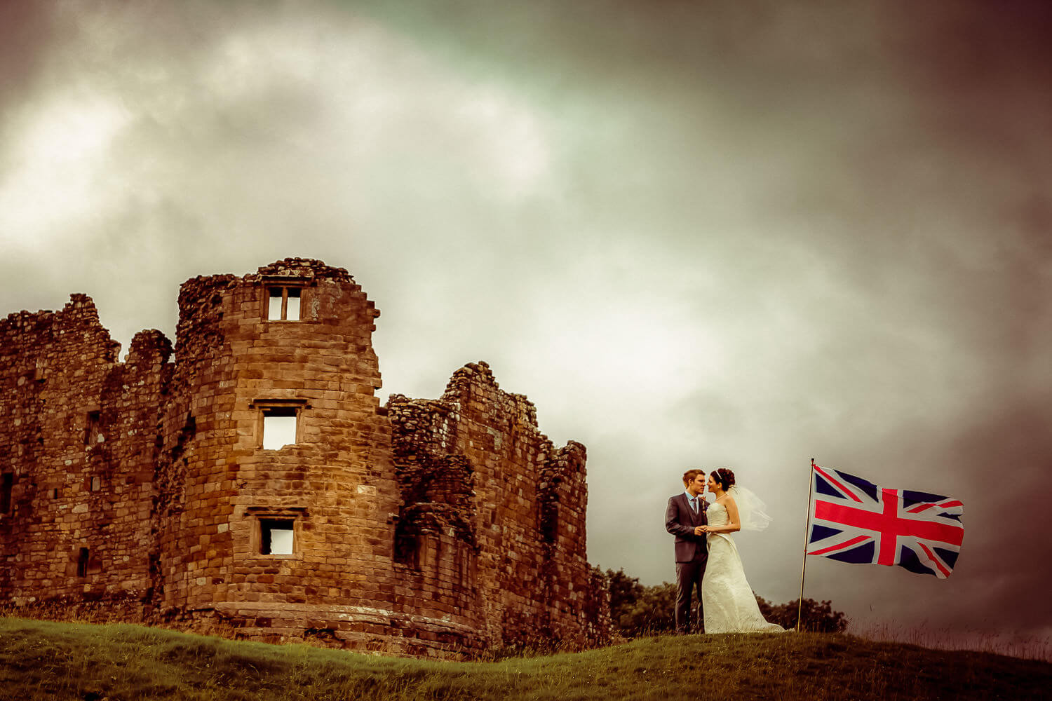 How to choose a wedding photographer UK. Bride and groom next to old castle with Union Jack flag