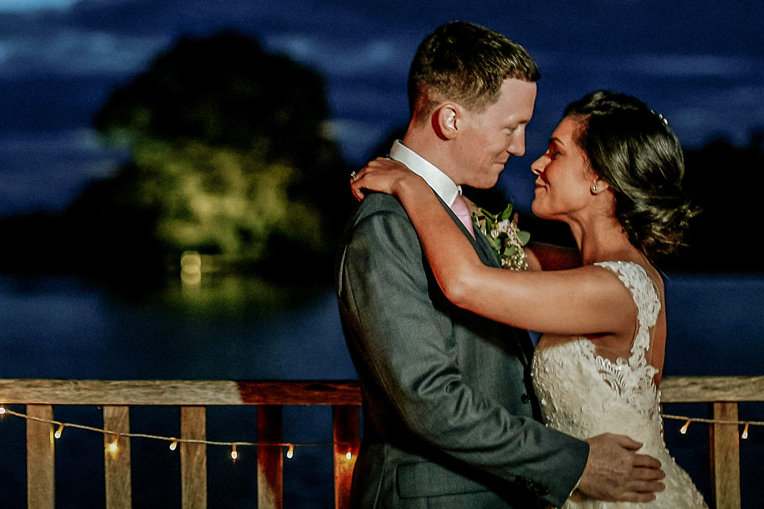 Bride and groom with evening sunset and lake and tree in background Sandhole Oak Barn wedding photographer
