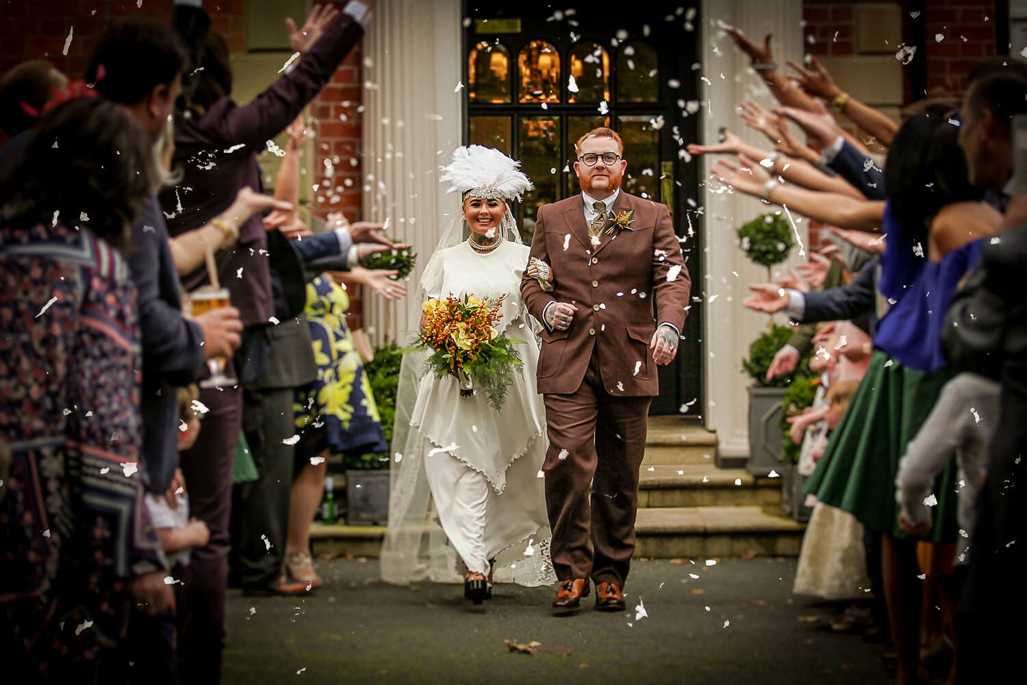Vintage bride and groom leaving Ashfield House under confetti shot. How to choose a wedding photographer