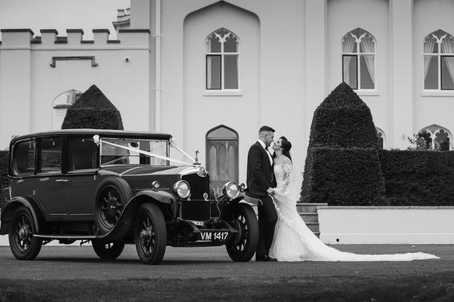 How to pick a wedding photographer UK. Bride and groom with old fashioned wedding car at Combermere Abbey