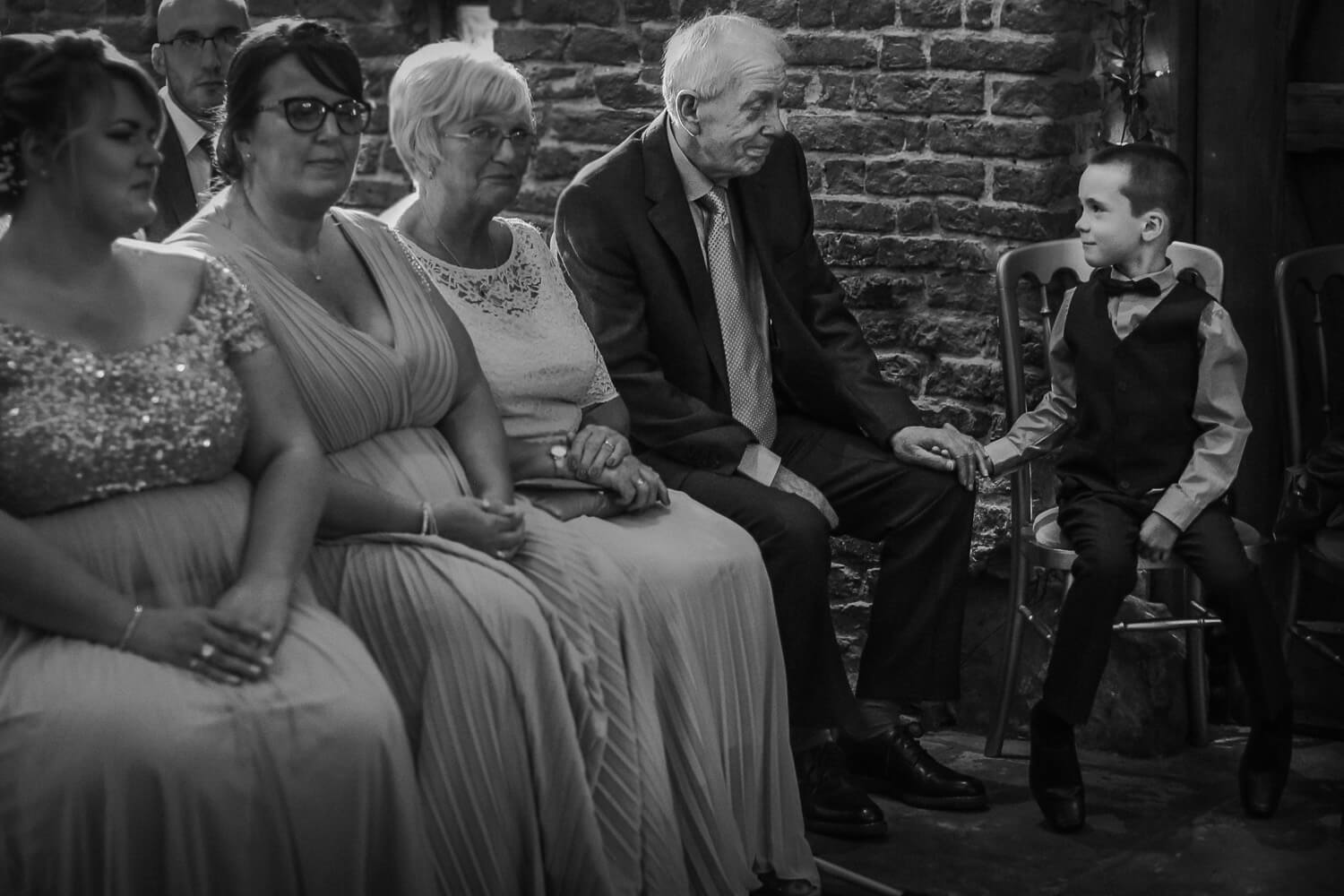 Little boy holding granddads hand during wedding ceremony. What is documentary wedding photography