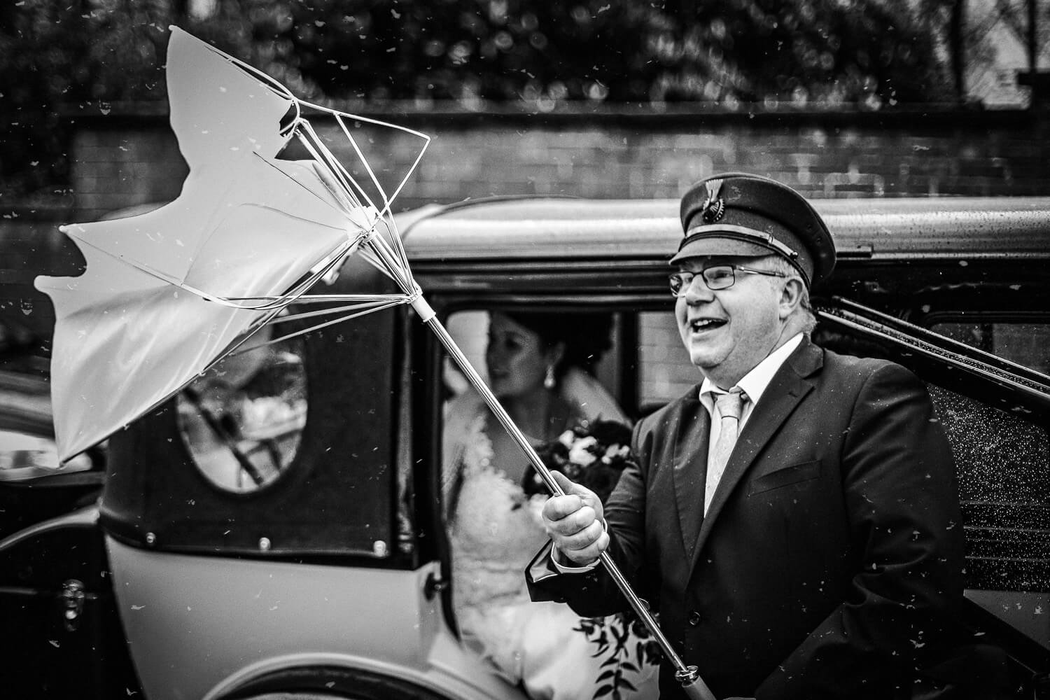 Wedding car driver holding umbrella as it blows inside out. Lancashire Documentary wedding photography explained
