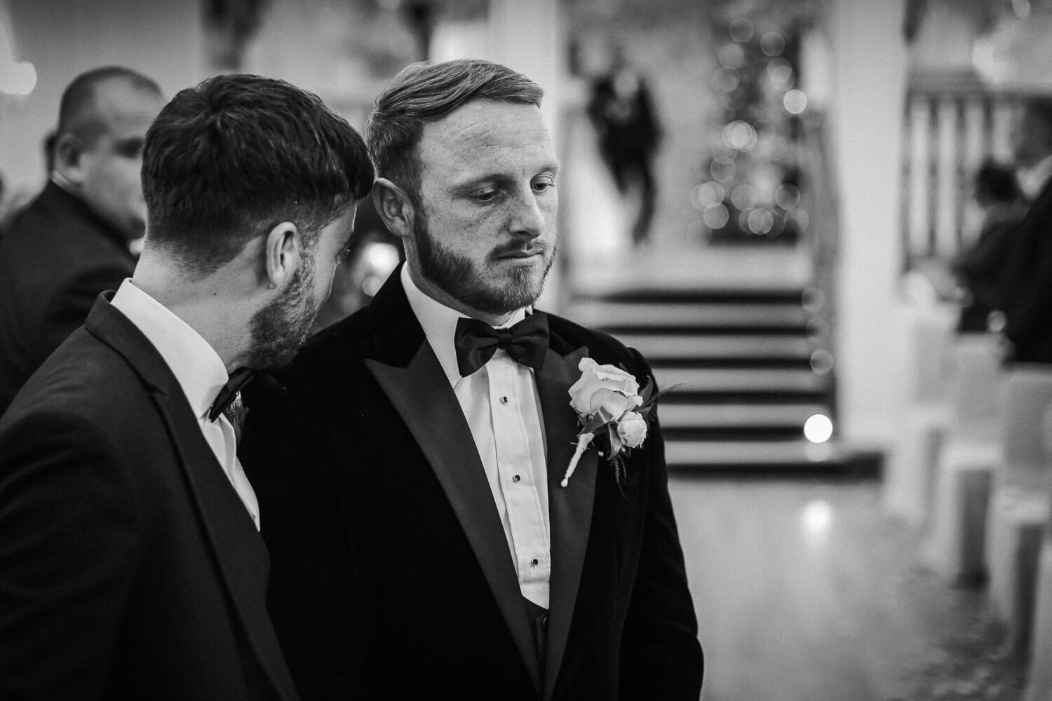 black and white photo of groom waiting for bride in ballroom at West Tower ceremony