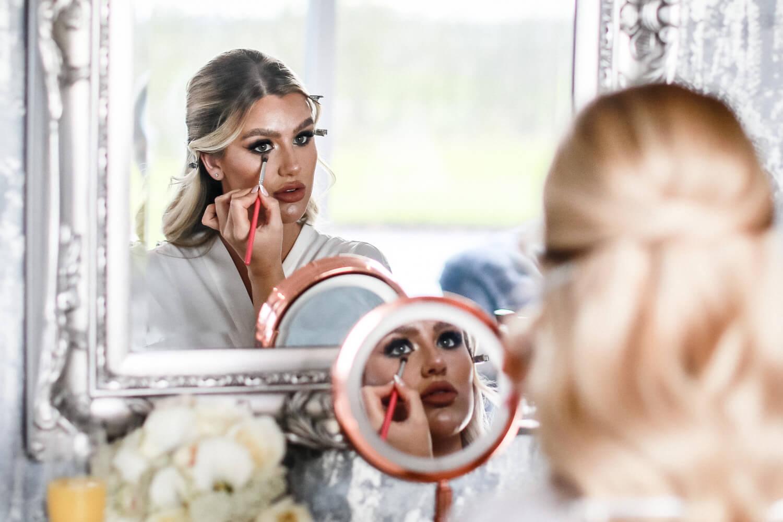 Bride doing makeup in mirror in Cristal suite