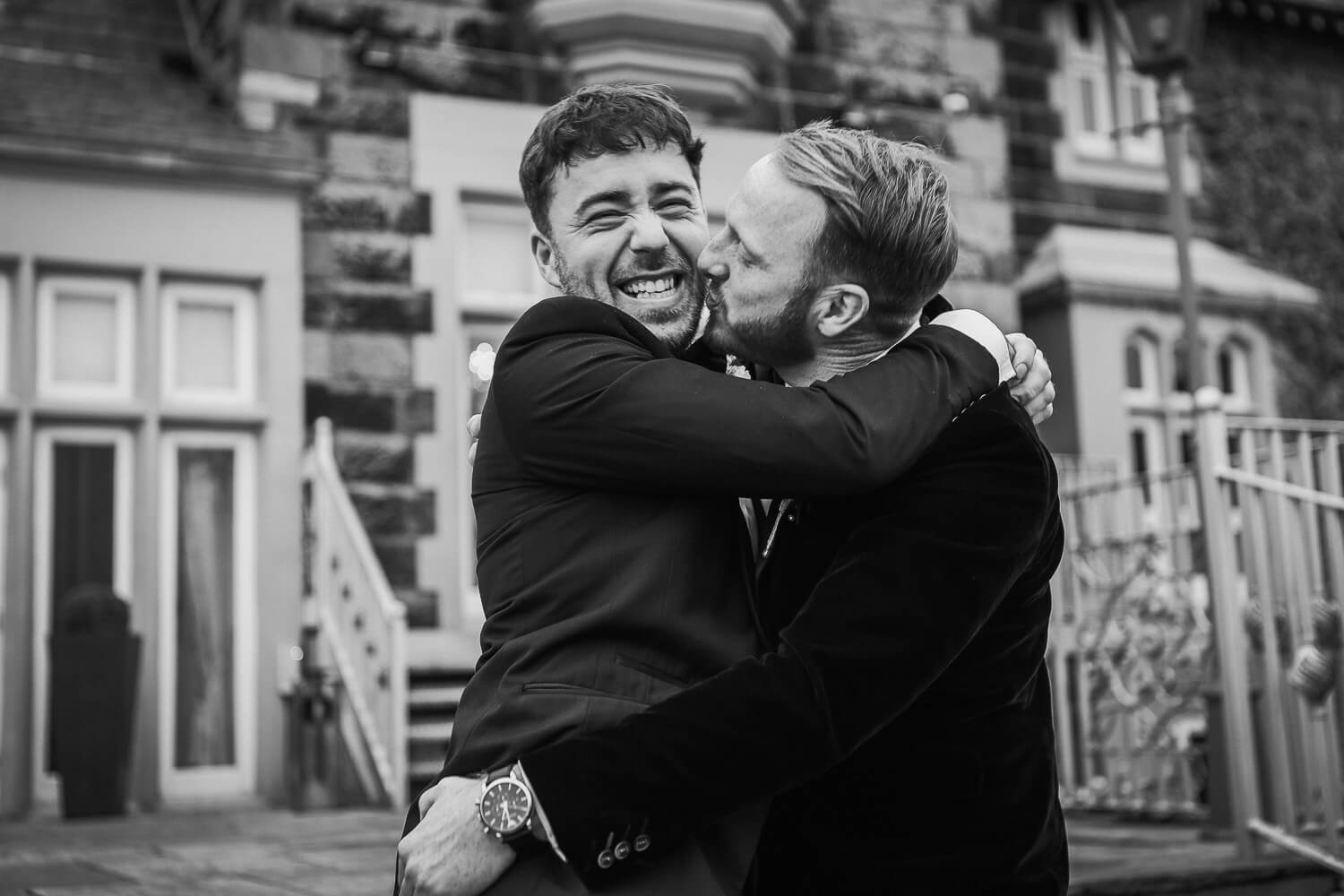 Groom playfully kissing bast man ion West tower steps