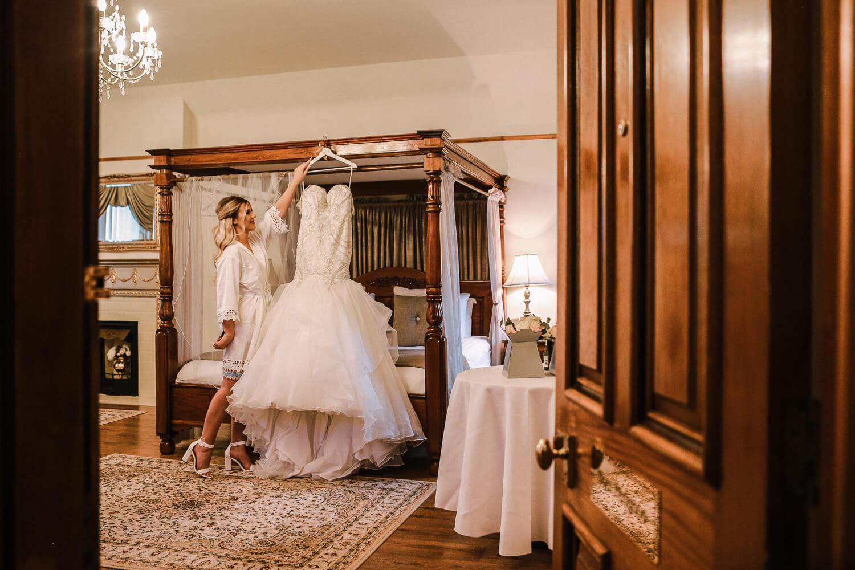 looking through the bridal suite door at bride hanging Maggie Sorretto wedding dress