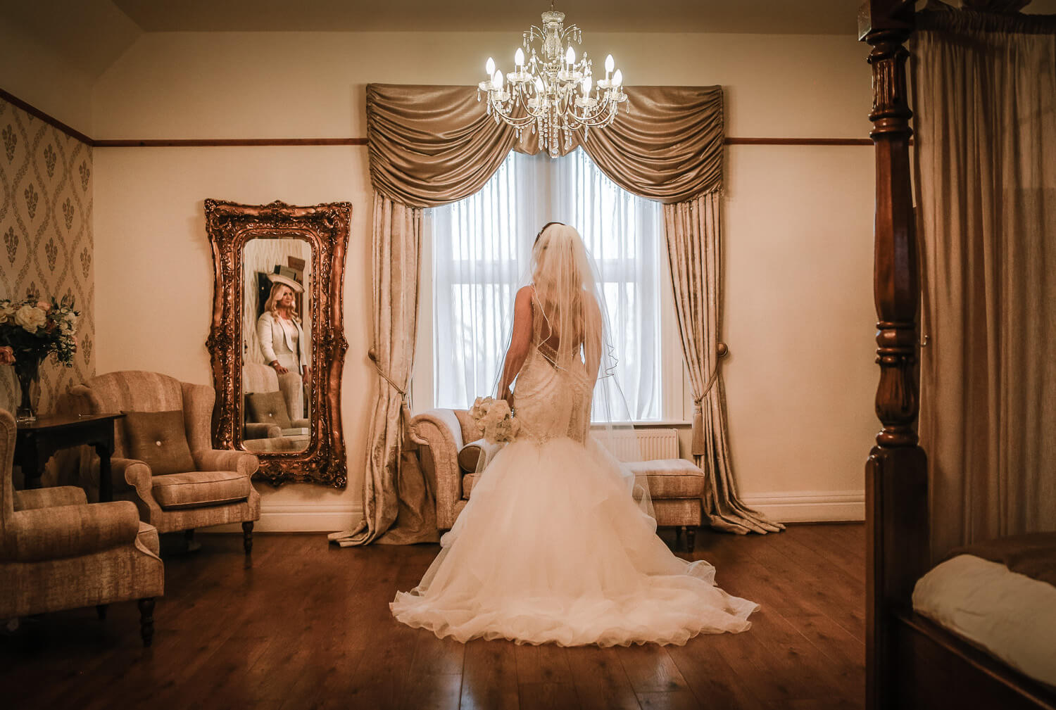 Bride in bridal West tower suite. Back of Maggie Sorretto dress and mum in reflection of mirror on wall